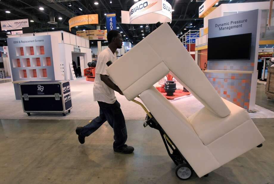 Workers remove booth props as the tear down process begins upon the conclusion of the Offshore Technology Conference at NRG on May 8, 2014, in Houston Tx. ( Mayra Beltran / Houston Chronicle ) Photo: Mayra Beltran, Houston Chronicle