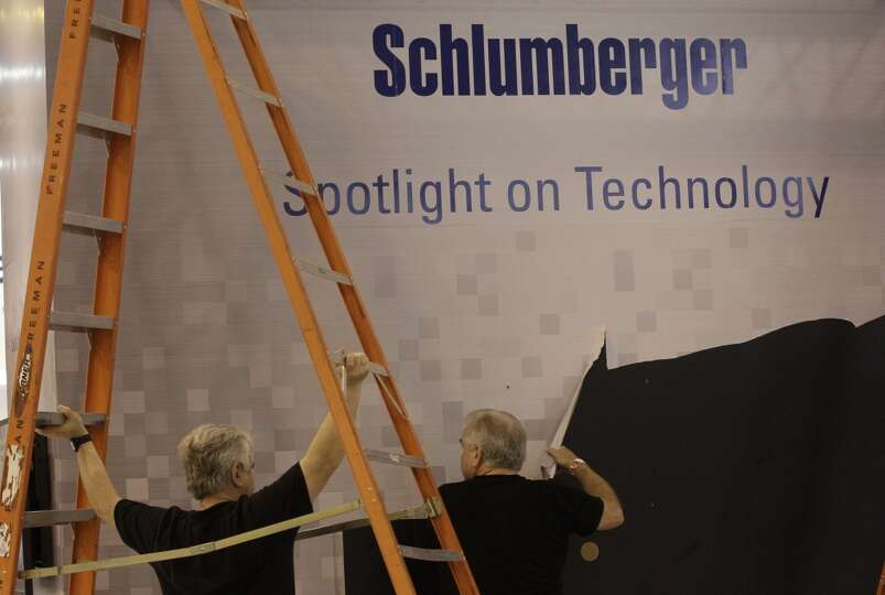 Work crews take down the Schlumberger booth at the conclusion of the Offshore Technology Conference