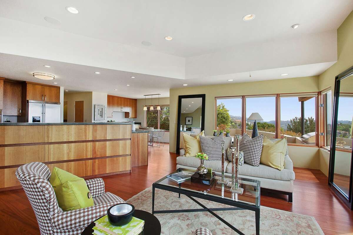 The great room features an open kitchen, hardwood floor and large windows framing picturesque views.