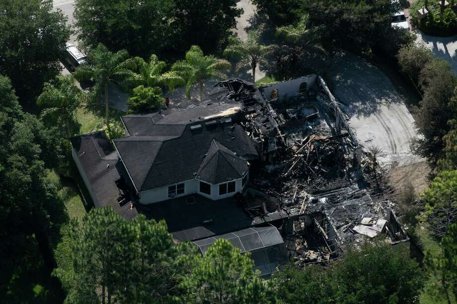 This aerial photo shows the burned out home on Thursday, May 8, 2014 in Tampa, Fla.  Authorities have said they think the fire at the five-bedroom home was intentionally set and that they found fireworks inside the home. Police have not said how the blaze started or who might be responsible. The home, which is owned by former tennis star James Blake, was engulfed in flames when firefighters responded Wednesday morning. Neighbors told police they heard explosions coming from it. Blake was renting the house to the a family and was not there at the time. (AP Photo/The Tampa Bay Times, Eve Edelheit)  TAMPA OUT; CITRUS COUNTY OUT; PORT CHARLOTTE OUT; BROOKSVILLE HERNANDO TODAY OUT Photo: Eve Edelheit, Associated Press / The Tampa Bay Times