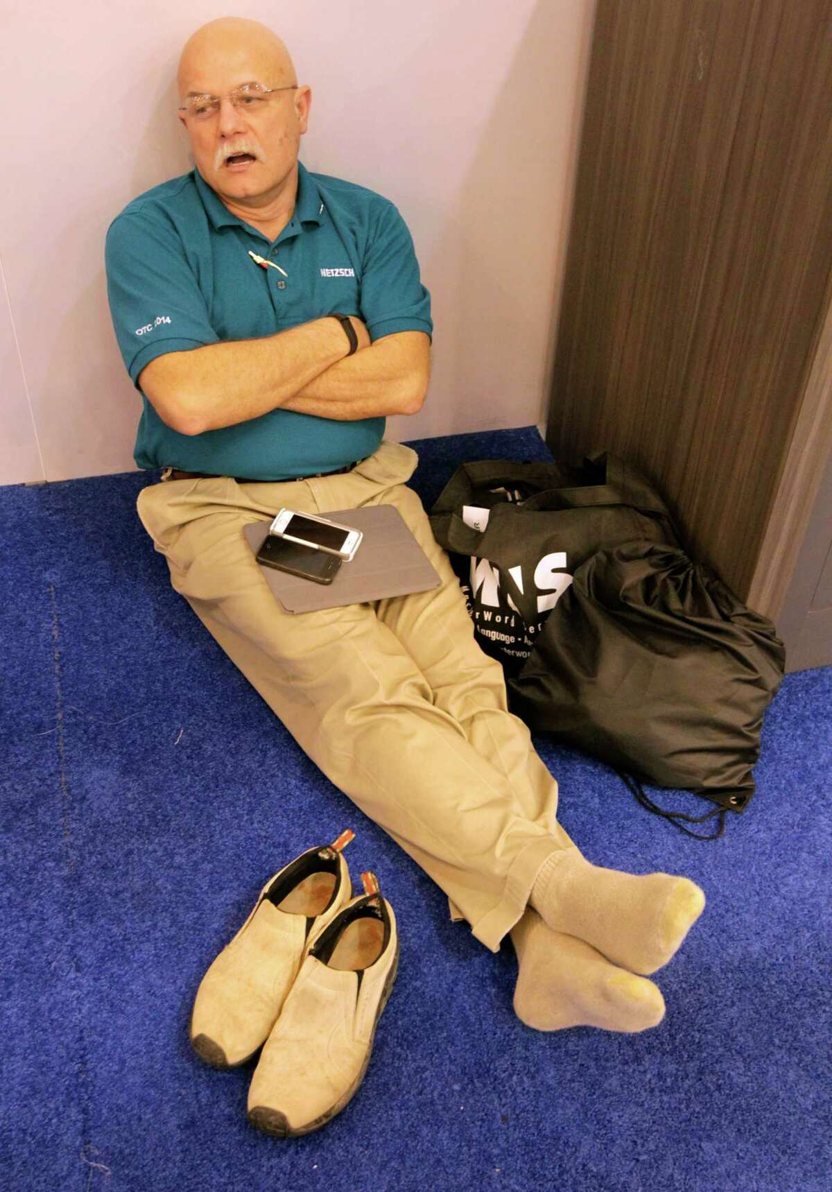 Julio Ferreira with Netzsch Pumps North America takes a moment Thursday to get off his feet at the conclusion of the Offshore Technology Conference at NRG Park.