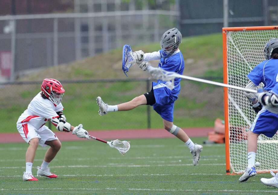 As Bronxville goalie Andrew Harwood, right, jumps high, Jamie Paradise of Greenwich, at left, goes low with his shot to score during the high school lacrosse match between Greenwich High School and Bronxville High School at Greenwich, Thursday night, May 8, 2014. Photo: Bob Luckey / Greenwich Time
