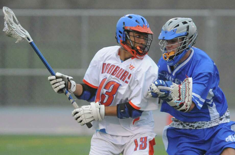 Danbury's Justin Warren, left, moves around Bunnell's Trevor Ross in the high school boys lacrosse game between Danbury and Bunnell at Danbury High School in Danbury, Conn. Thursday, May 8, 2014. Photo: Tyler Sizemore / The News-Times