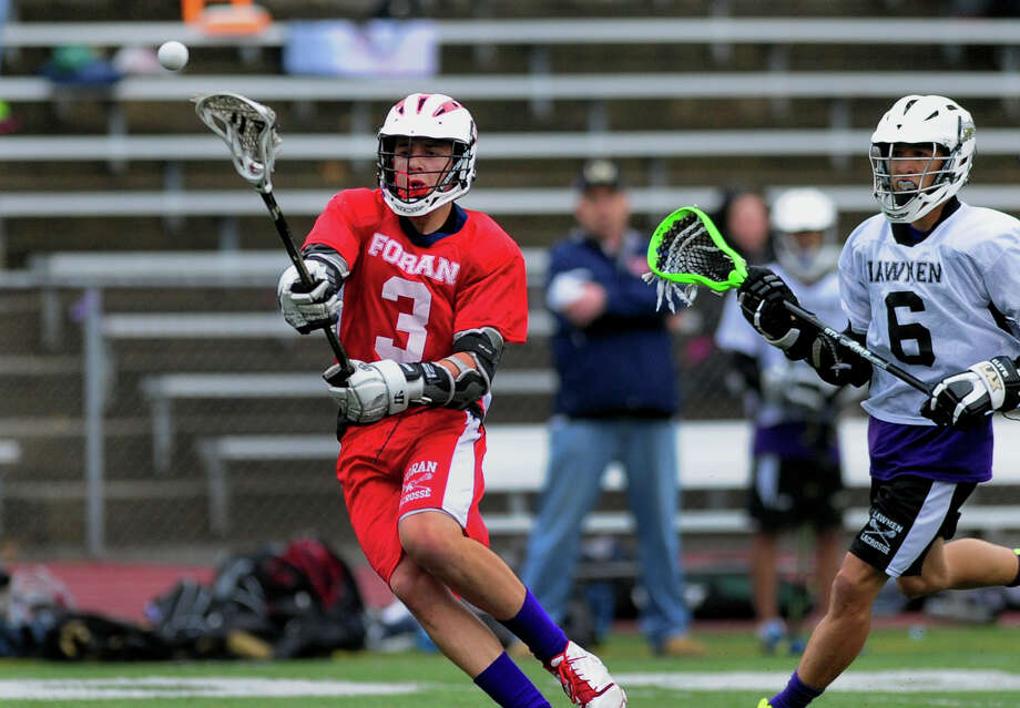 Foran's Paul Mirmina slings the ball to the goal for a point, during boys lacrosse action against Jonathan Law in Milford, Conn. on Thursday May 8, 2014. Unable to block Mirmina in time at right is Law's Chris Mercaldo. Photo: Christian Abraham / Connecticut Post