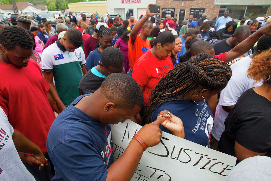 Protesters bow their heads in prayer over the death of Pearlie Golden to close a rally in front of the Hearne Police Department on Thursday. Photo: Cody Duty, Staff / © 2014 Houston Chronicle
