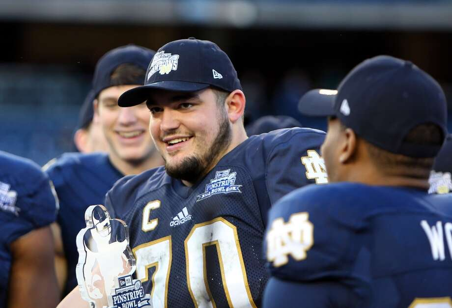 Zack Martin #70 of the Notre Dame Fighting Irish runs celebrates after being named MVP of the New Era Pinstripe Bowl after the team's win over the Rutgers Scarlet Knights during the New Era Pinstripe Bowl at Yankee Stadium on December 28, 2013 in the Bronx Borough of New York City. Photo: Nate Shron, Getty Images
