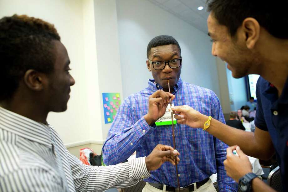 Foster High School student Michael Elege draws chocolate syrup through eight connected straws during an experiment at the Offshore Technology Conference meant to show the force needed to pull oil from a well. Photo: Marie D. De Jesus, Staff / © 2014 Houston Chronicle