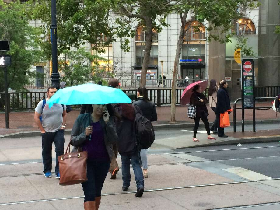 Pedestrians in downtown San Francisco take shelter under umbrellas during Thursday's drizzle, which is expected to clear by Friday morning. (Will Kane/The Chronicle)