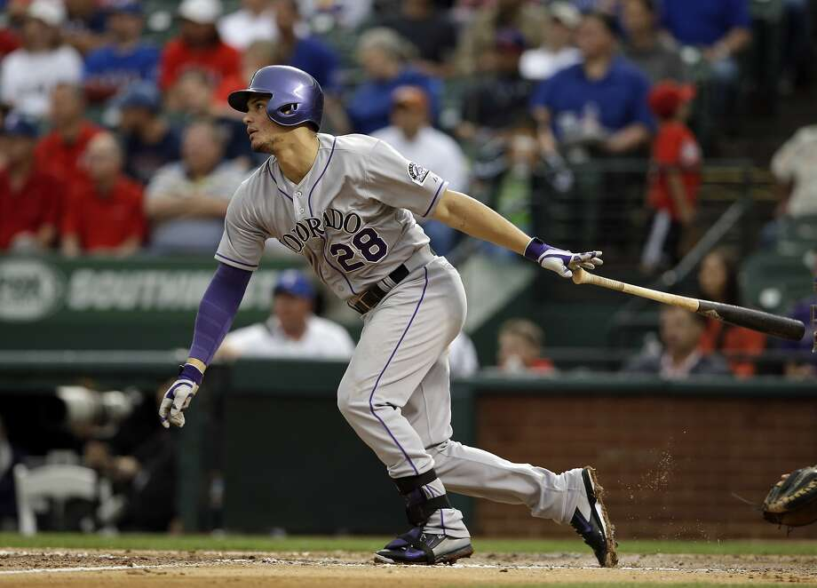 Colorado's Nolan Arenado singles against Rangers starter Matt Harrison in the third inning to extend his hitting streak to a franchise-record 28 games. Photo: Tony Gutierrez, Associated Press