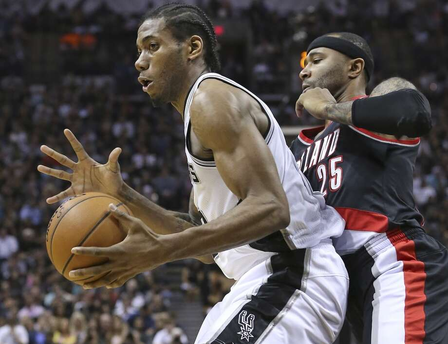 Kawhi Leonard puts a grip on the ball before pivoting in the lane against Mo Williams as the San Antonio Spurs play the Portland Trailblazers in game 2 of the Western Conference Semifinals at the AT&T Center on May 8, 2014.
