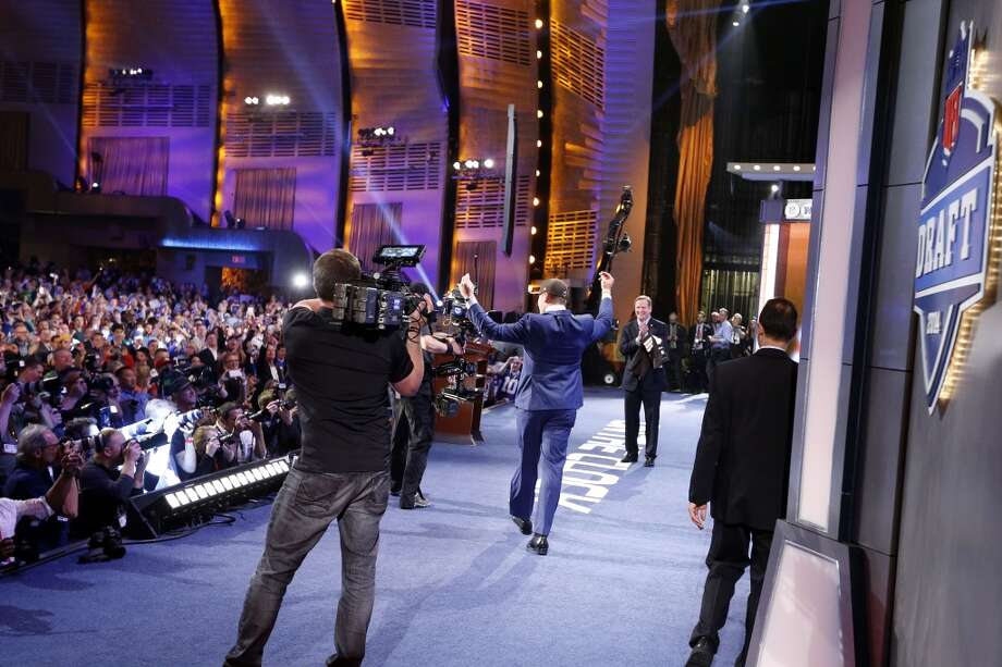 Johnny Manziel, from Texas A&M, celebrates as he walks onstage after being selected 22nd overall by the Cleveland Browns during the first round of the NFL football draft, Thursday, May 8, 2014, at Radio City Music Hall in New York. Photo: Jason DeCrow, Associated Press
