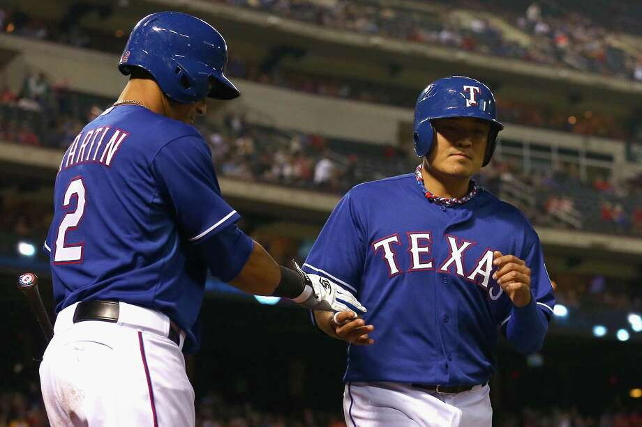 Texas' Shin-Soo Choo (right) greets Leonys Martin after scoring on a wild pitch in Arlington. Photo: Tom Pennington / Getty Images / 2014 Getty Images
