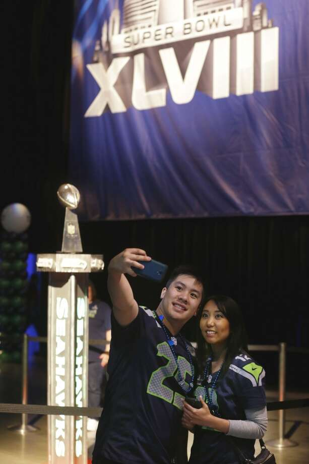 "Seattle Seahawks fans Kevin Chan, left, and Sarah Rithvixay, right, take a ""selfie"" photograph with the Super Bowl Vince Lombardi Trophy as they attend the Seattle Seahawks NFL football draft party, Thursday, May 8, 2014 at the CenturyLink Field Events Center in Seattle. Photo: Ted S. Warren, Associated Press"