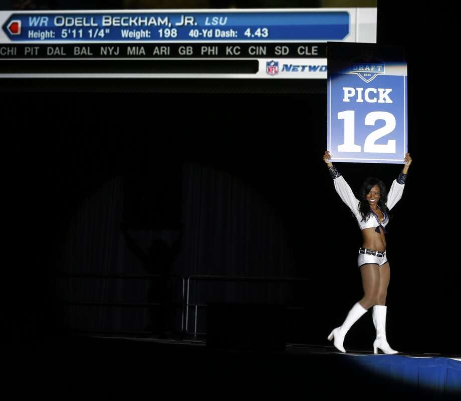 A Seattle Seahawks Sea Gal cheerleader carries a sign announcing the 12th pick of the first round of the NFL football draft, the selection by the New York Giants of Louisiana State wide receiver Odell Beckham Jr. during the Seattle Seahawks NFL football draft party, Thursday, May 8, 2014 at the CenturyLink Field Events Center in Seattle. Photo: Ted S. Warren, Associated Press