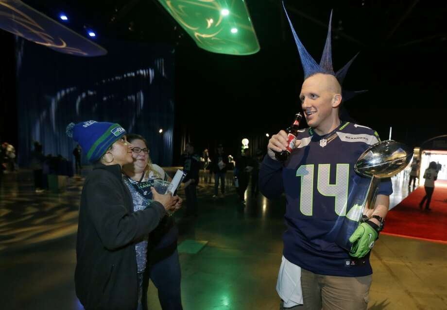 "Seattle Seahawks fan Phil ""Mr. Mohawk"" Andruss, right, holds his replica of the Vince Lombardi Trophy as he attends the Seattle Seahawks NFL football draft party, Thursday, May 8, 2014 at the CenturyLink Field Events Center in Seattle. Photo: Ted S. Warren, Associated Press"