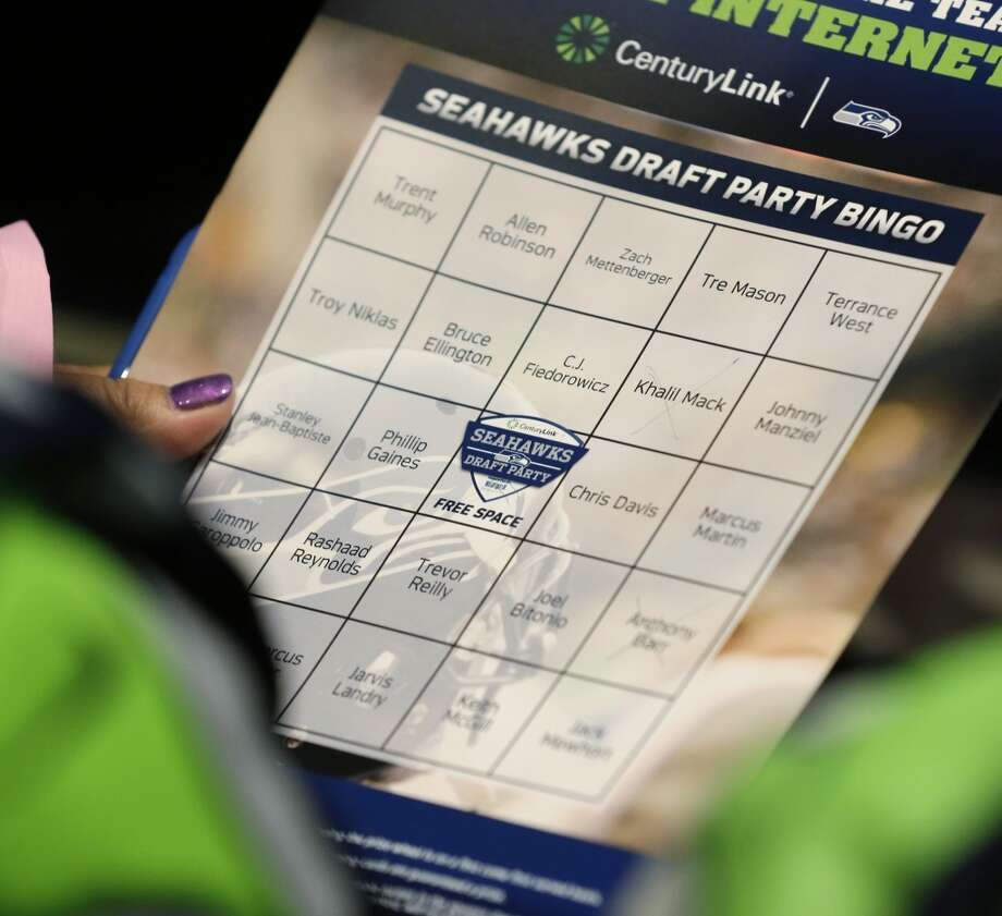 "A fan holds a ""Draft Party Bingo"" card at the Seattle Seahawks NFL football draft party, Thursday, May 8, 2014 at the CenturyLink Field Events Center in Seattle. As players are drafted, fans try to complete rows for a Bingo. Photo: Ted S. Warren, Associated Press"
