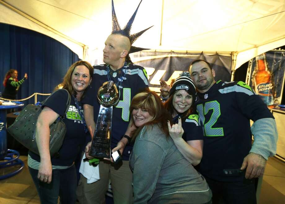 "Seattle Seahawks fans pose for a photo with Phil ""Mr. Mohawk"" Andruss , second from left, and his replica of the Vince Lombardi Trophy at the Seattle Seahawks NFL football draft party, Thursday, May 8, 2014 at the CenturyLink Field Events Center in Seattle. Photo: Ted S. Warren, Associated Press"