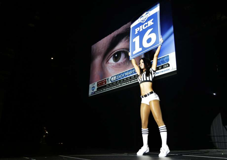 A Seattle Seahawks Sea Gals cheerleader carries a sign to announce the 16th pick in the first round of the NFL football draft, the selection of Notre Dame offensive tackle Zack Martin by the Dallas Cowboys, Thursday, May 8, 2014 during the Seahawks draft party at the CenturyLink Field Events Center in Seattle. Photo: Ted S. Warren, Associated Press
