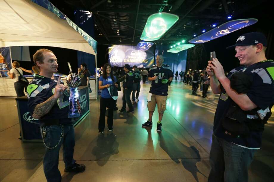 Seahawks fan Dwight Kaestner, left, holds a replica of the Vince Lombardi Trophy as Bryce Walker, right, takes his photo at the Seattle Seahawks NFL football draft party, Thursday, May 8, 2014 at the CenturyLink Field Events Center in Seattle. Photo: Ted S. Warren, Associated Press