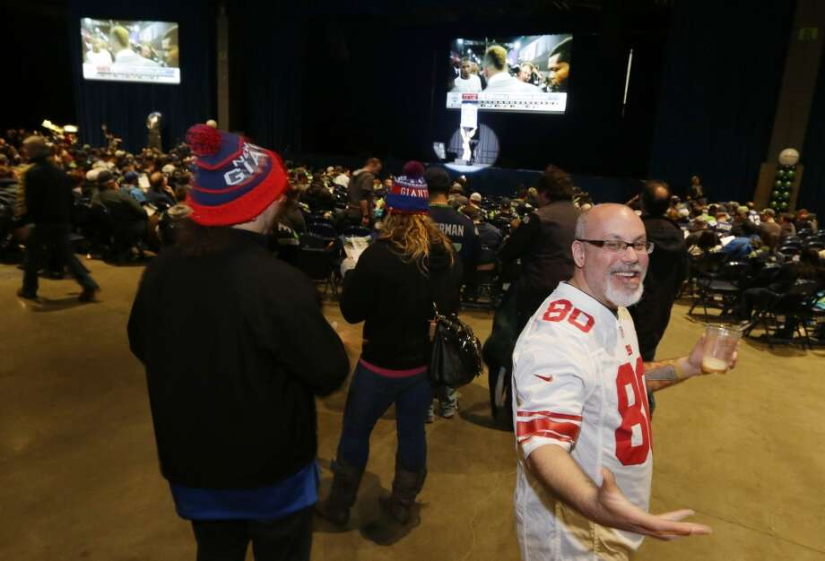 New York Giants fan Greg Greenstein, right, of North Bend, Wash., reacts to the Giants picking Louisiana State wide receiver Odell Beckham Jr. in the first round of the NFL football draft as he attends the Seattle Seahawks NFL football draft party, Thursday, May 8, 2014 at the CenturyLink Field Events Center in Seattle. Photo: Ted S. Warren, Associated Press