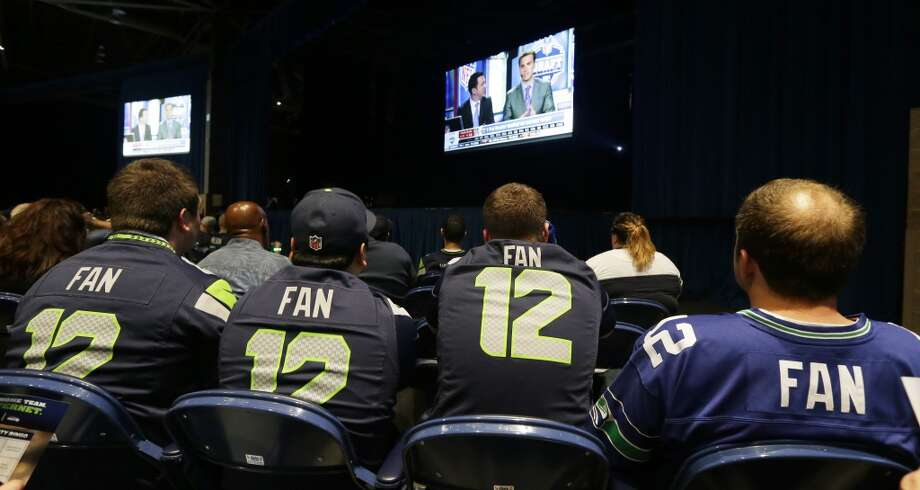 "Spectators wearing Seattle Seahawks ""12th Man"" fan jerseys watch a broadcast of the NFL football draft at the Seattle Seahawks NFL football draft party, Thursday, May 8, 2014 at the CenturyLink Field Events Center in Seattle. Photo: Ted S. Warren, Associated Press"