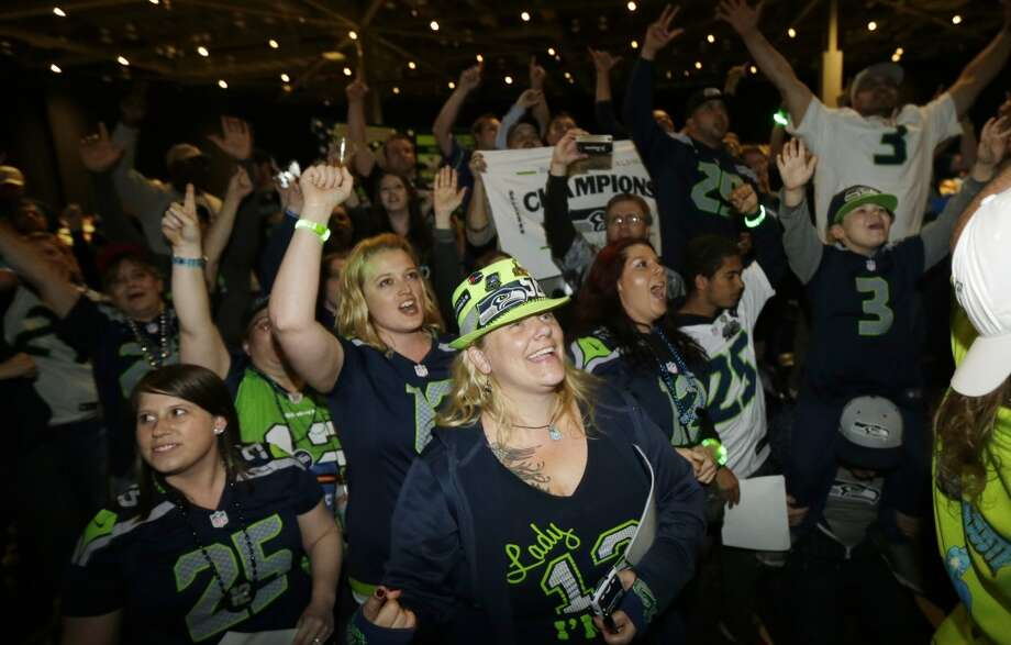 Seattle Seahawks fans cheer just before it was announced that the Seahawks traded their 32nd pick in the first round of the NFL football draft to the Minnesota Vikings, Thursday, May 8, 2014, during the Seahawks draft party at the CenturyLink Field Events Center in Seattle. Photo: Ted S. Warren, Associated Press