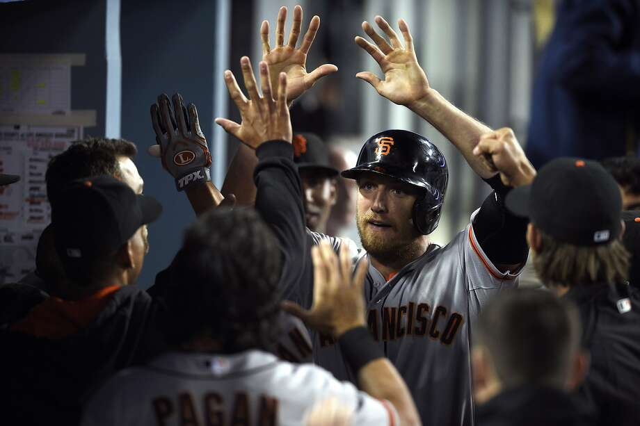 Hunter Pence celebrates in the dugout after scoring on Brandon Belt's 10th-inning single. Photo: Kelvin Kuo, Associated Press