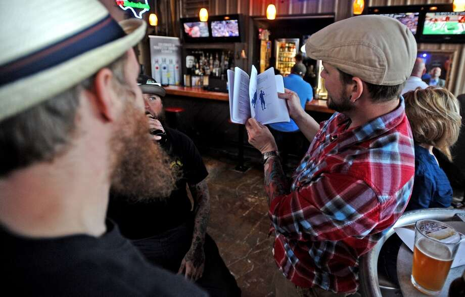 Michael Degarmo shows off a book that belongs to his wife, Melissa, titled Beer Awesomeness during American Craft Beer Week at Madison's on Tuesday, May 14, 2013. Photo taken: Randy Edwards/The Enterprise