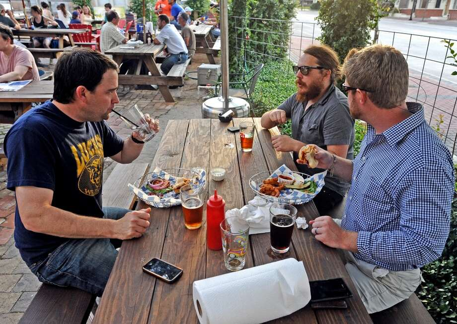 Ronnie Hardin, left, Wes Hardin, center, and Tyler Blount, right, claim a table on the patio to enjoy dinner and brews during American Craft Beer Week at Luke's on Wednesday, May 16, 2013. Photo taken: Randy Edwards/The Enterprise