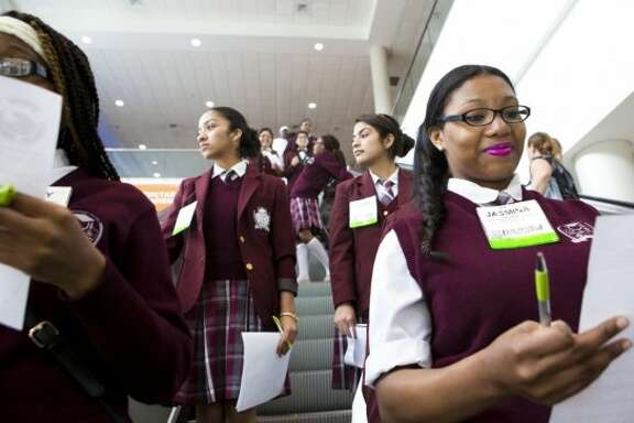 Jasmina Thomas, right, a Young Women's College Preparatory Academy student revises a list of questions as she and her classmates take the escalators to the conference exhibition floor as part of the High School STEM event, Thursday, May 8, 2014, in Houston.