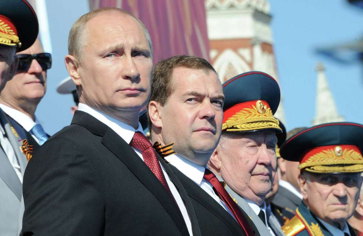 TOPSHOTS Russia's President Vladimir Putin (L) and Prime Minister Dmitry Medvedev (2nd L) attend a Victory Day parade at the Red Square in Moscow, on May 9, 2014. Thousands of Russian troops marched today in Red Square to mark 69 years since victory in World War II in a show of military might amid tensions in Ukraine following Moscow's annexation of Crimea.AFP PHOTO/ RIA-NOVOSTI/ POOL/ MIKHAIL KLIMENTYEVMIKHAIL KLIMENTYEV/AFP/Getty Images ORG XMIT: ?.????? ?