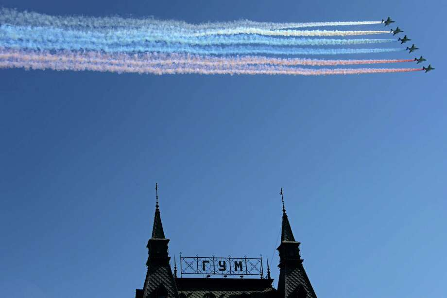 TOPSHOTS Russian Sukhoi Su-25 ground-attack aircraft release smoke in the colours of the Russian flag while flying above  the Red Square in Moscow, on May  9, 2014, during a Victory Day parade. Thousands of Russian troops marched today in Red Square to mark 69 years since victory in World War II in a show of military might amid tensions in Ukraine following Moscow's annexation of Crimea. AFP PHOTO / KIRILL KUDRYAVTSEVKIRILL KUDRYAVTSEV/AFP/Getty Images Photo: KIRILL KUDRYAVTSEV, Getty / AFP