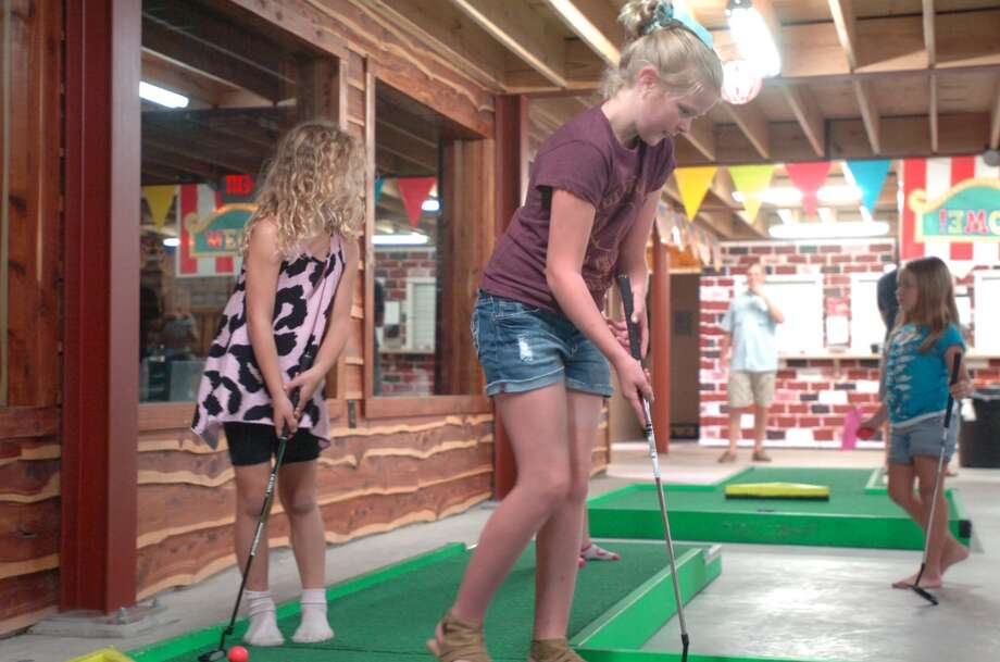 Elise Griffin and Amelia Sims play the green as Graci Jeans and Savannah Ivey await their turns on the miniature golf course at Elise's Play House. The indoor amusement center at Nutty Jerry's in Winnie opens to the public next Saturday. Photo: Sarah Moore