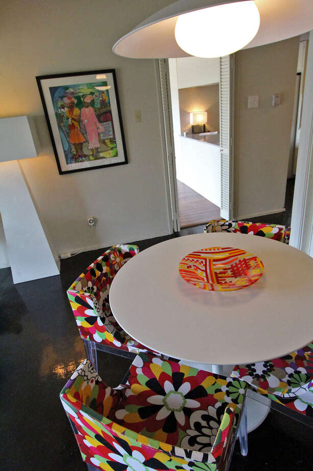 Four Kartell chairs in sporting a vivid print circle a table in the den. / ALL RIGHTS RESERVED UNLESS OTHERWISE SPECIFIED