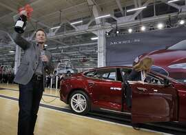 Tesla CEO Elon Musk holds up a bottle of wine as a gift from one of the first customers, right, during a rally at the Tesla factory in Fremont, Calif., Friday, June 22, 2012.  The first mass-market sedans offered by electric car maker Tesla are now on the road. (AP Photo/Paul Sakuma)