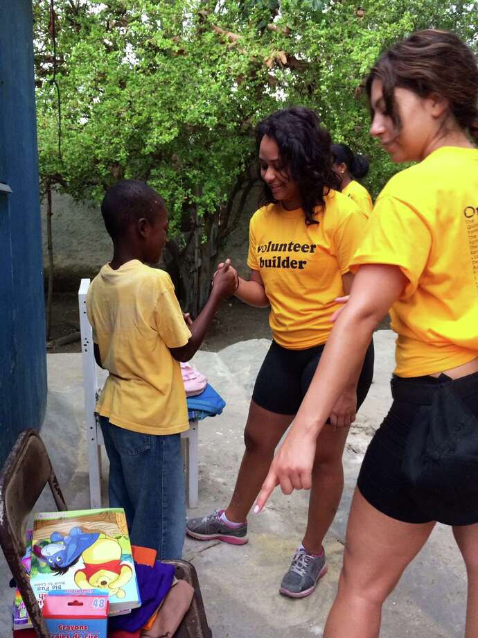 """Danbury residents  Leticia Holanda and Rawan Hage are seen in Haiti with Jameson, a boy whose family had been living under a ripped up tarp. Holanda and Hage joined Danbury resident Patty Reyes in helping to build a home for the family. The women brought toys and coloring books for children in the area and are seen here reaching toward Jameson to play a  game of """"thumb war"""" during some down time on the build site. Photo: Contributed Photo / The News-Times Contributed"""