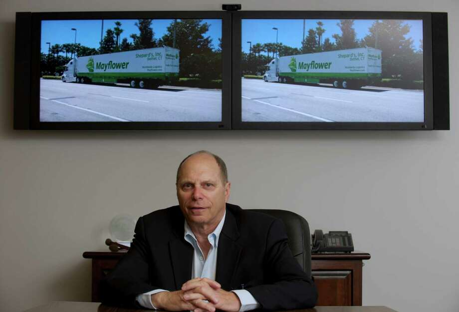 Michael W. Goodman, President, of Shepard's Inc., a moving company based in Bethel, Conn that is divided into three divisions, household relocation services, commercial logistics and warehousing & fulfillment, on Friday, May 9, 2014. Photographs behind him are of the new look the companies trucks will be displaying. Photo: H John Voorhees III / The News-Times Freelance
