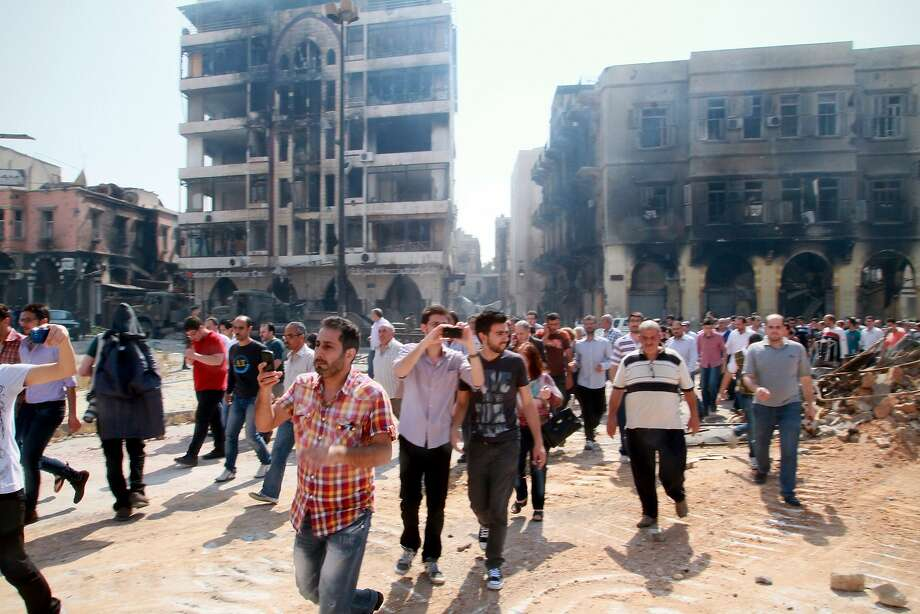 In this photograph made on a government-led media tour, Syrian civilians return to Homs, Syria on Friday, May 9, 2014, where bulldozers cleared rubble from the streets of battle-scarred districts in the central Syrian city after government troops entered the last rebel-held neighborhoods as part of an agreement that also granted opposition fighters safe exit from the city. (AP Photo) Photo: Uncredited, Associated Press