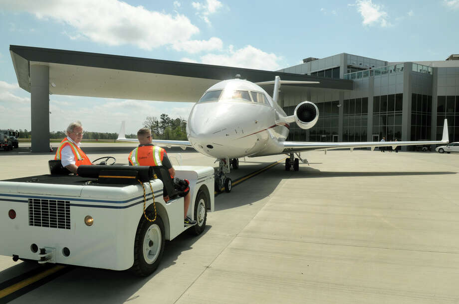 David Christy, from left, of Montgomery, and Allen Garcia, of Spring, tow a Challenger 605 to a hangar at Galaxy FBO at Lone Star Executive Airport in Conroe. Photo: Jerry Baker, Freelance