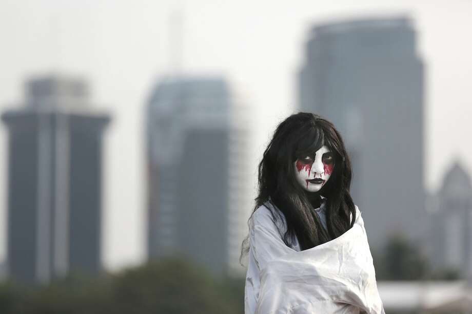 Ghost for hire:A Jakarta street performer dressed up as a traditional Indonesian ghost known as 