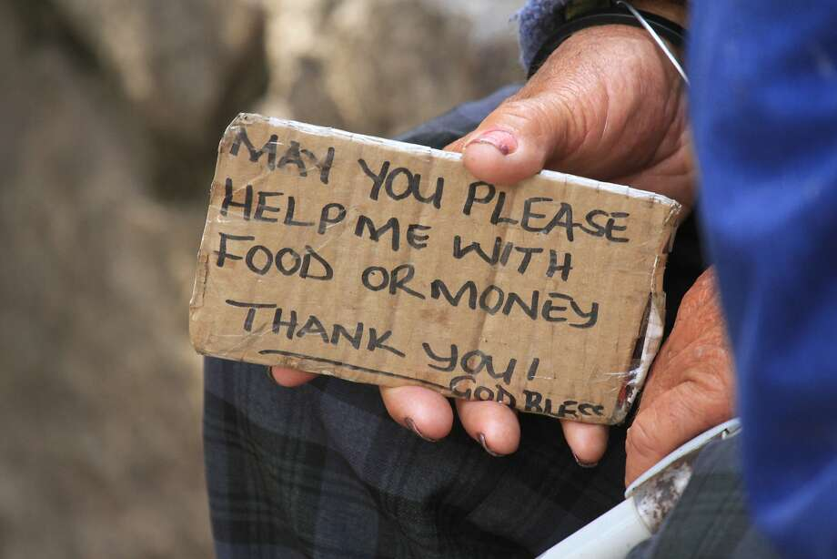 The panhandling sign that fits in your pocket: In Zimbabwe, an elderly Zimbabwe man holds 