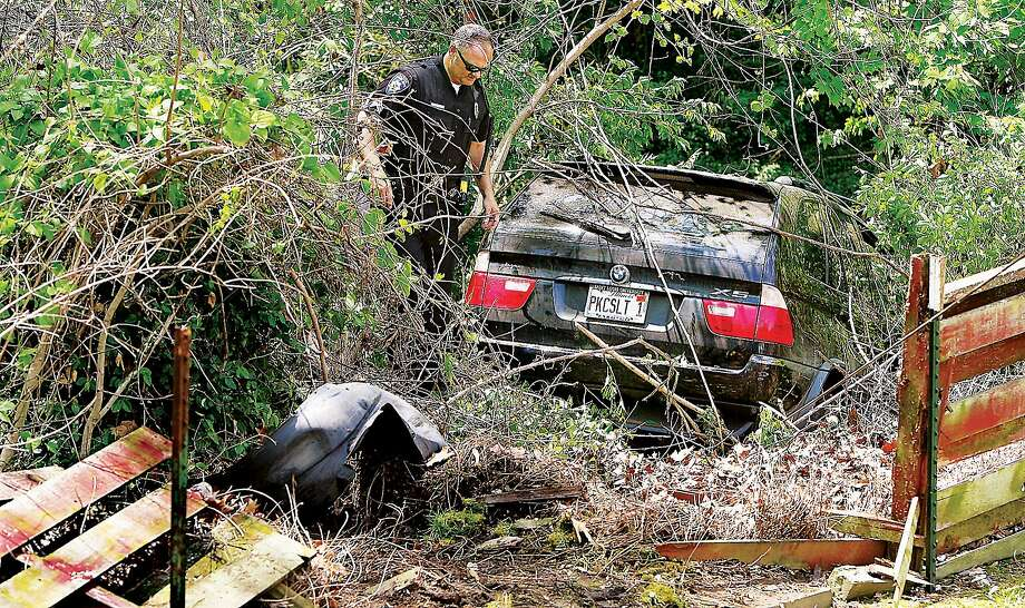 Beemer in the bushes: Alton Police Sgt. Shane Gibbs examines a BMW SUV that inadvertently 
