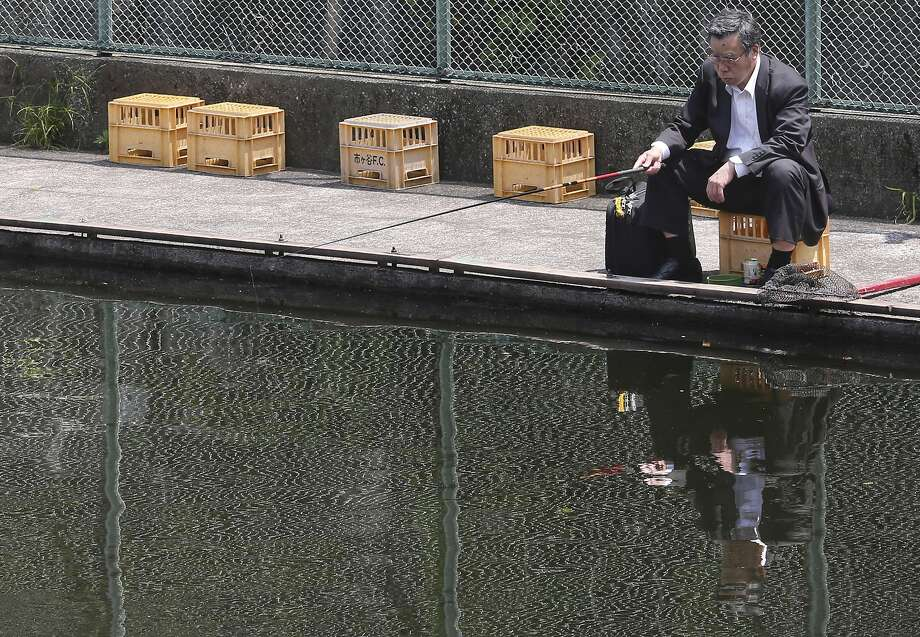 Fishing for sales leads?A businessman tries his luck at an artificial pond in 