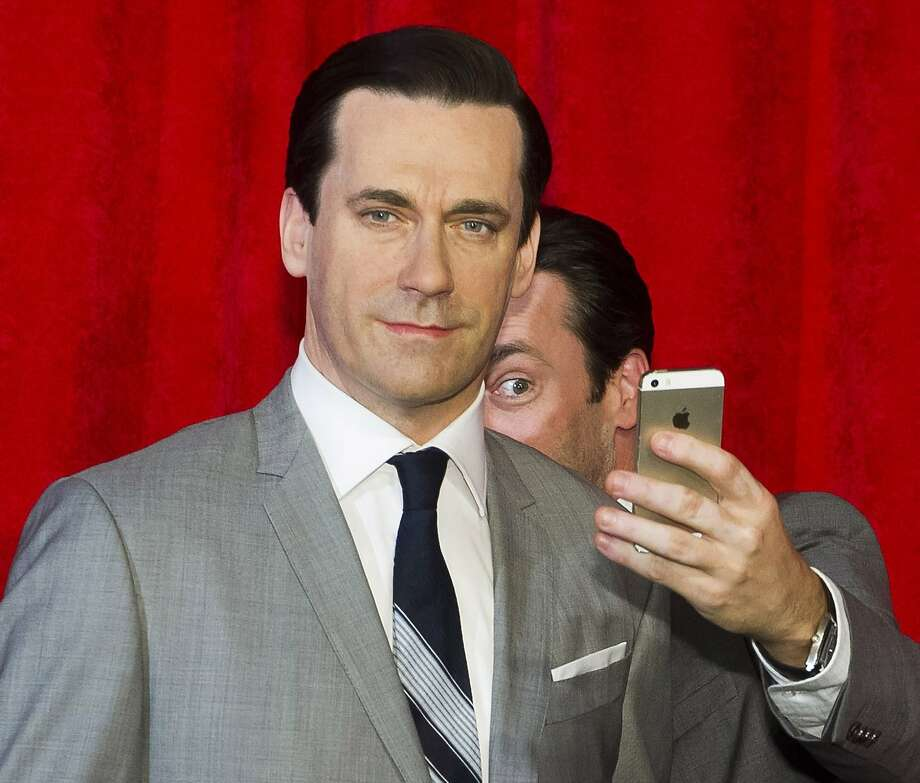 Jon Hamm, right, takes a selfie at the unveiling of his wax figure at Madame Tussauds on Friday, May 9, 2014 in New York. (Photo by Charles Sykes/Invision/AP) Photo: Charles Sykes, Associated Press