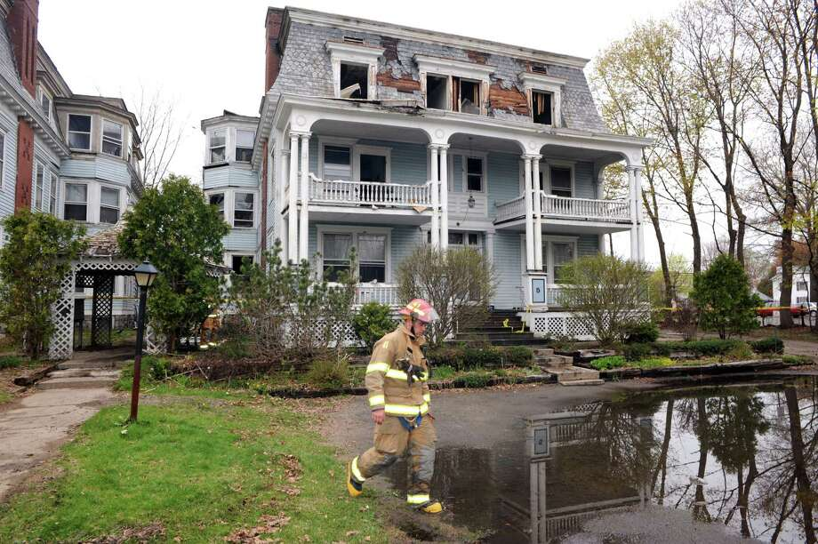 A firefighter walks past the scene of a fire at 5 Sherman Avenue on Friday May 9, 2014 in Glens Falls, N.Y. (Michael P. Farrell/Times Union) Photo: Michael P. Farrell / 00026842A