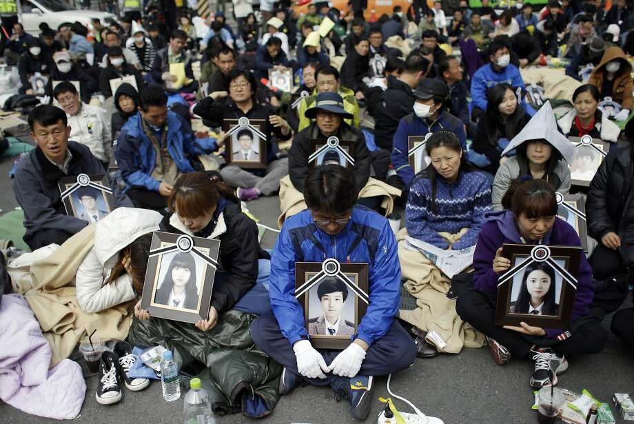 Grieving families demand an audience:Relatives hold portraits of the victims of the 