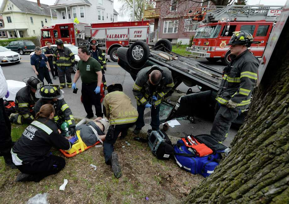 The victim of a rollover crash is attended to by the Albany Fire and EMS units Friday afternoon May 9, 2014, at the corner of North Main Street and Central Avenue.  According to officials at the scene, the drug Narcan was used to revive the victim at the scene.  Drug paraphernalia was found in the car at the scene. (Skip Dickstein / Times Union) Photo: Skip Dickstein