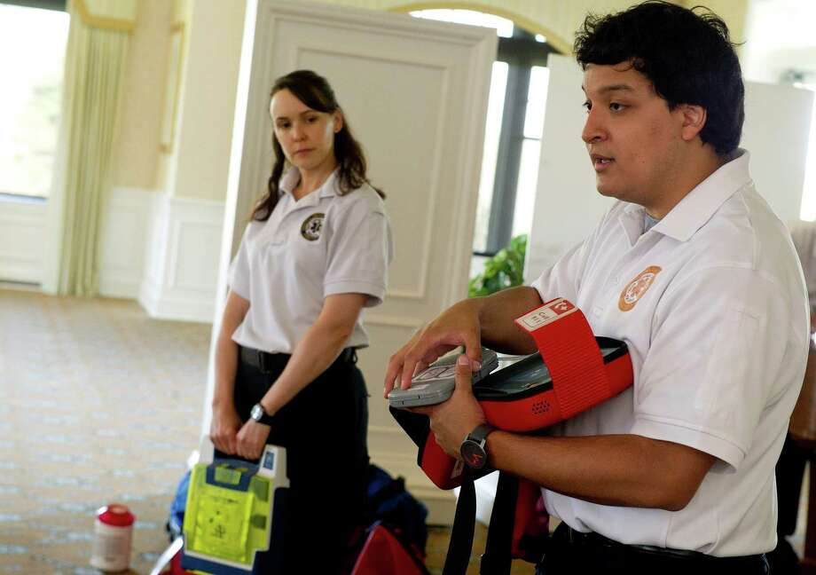 Greenwich EMS's Lindsey Taylor, left, and Andres Moreira, right, hold defibrillators as they hold a training session at Tamarack Country Club in Greenwich, Conn., on Wednesday, May 7, 2014. Photo: Lindsay Perry / Stamford Advocate