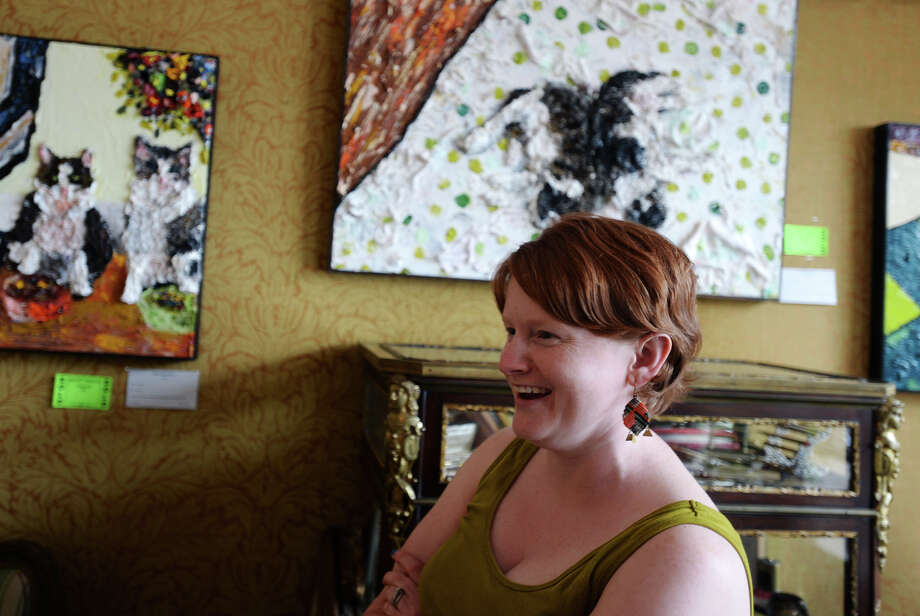 "Sarah Hamilton talks about her interest in serial killer and cats as subjects for her art Thursday. Hamilton's display of feline-related art -- including her serial killer series entitled ""Serial Catter"" -- finished up its showing at Finder's Fayre on Thursday afternoon.  Photo taken Thursday 5/8/14 Jake Daniels/@JakeD_in_SETX Photo: Jake Daniels / ©2014 The Beaumont Enterprise/Jake Daniels"