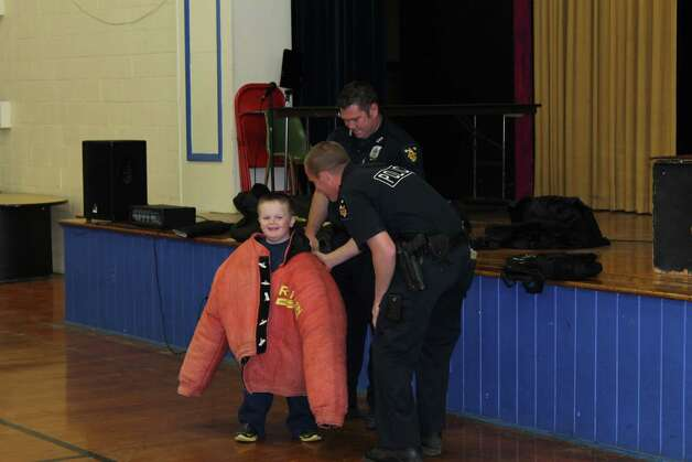 Three officers and two K-9s from the Troy Police Department visited St. Augustine's School to put on a training demonstration on Monday, May 5.  Ryan Horn, a kindergartener at St. Augustine?s School, wears a K-9 training jacket. (Submitted by St. Augustine's School)